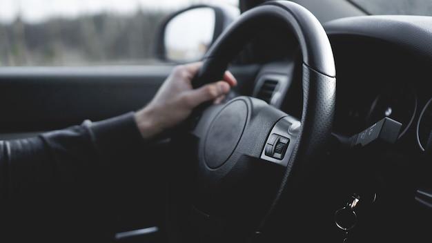 Widok wnętrza samochodu z czarnym salonem. zbliżenie człowieka ręce trzymając kierownicę podczas jazdy samochodem