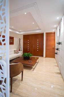 Widok wnętrza wejścia do domu z drewnianym centralnym stołem, domem i dekoracją