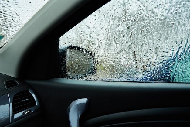 Widok wnętrza z samochodu pokrytego marznącym deszczem. lód na przedniej szybie samochodu.