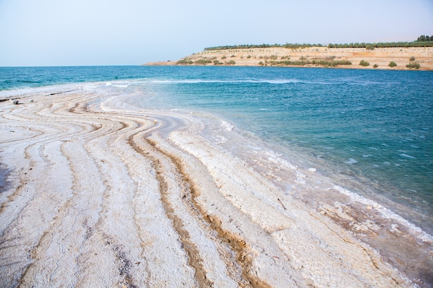 Widok wybrzeża morza martwego o zachodzie słońca w jordanii. kryształy soli o zachodzie słońca