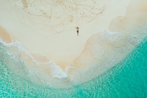 Widok wyspy daku z nieba. mężczyzna relaksuje brać sunbath na plaży. fotografia brać z trutniem nad piękna scena. koncepcja podróży, przyrody i krajobrazów morskich