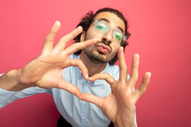 Widok z bliska pod wrażeniem młodego przystojnego mężczyzny w okularach, patrząc z przodu, robi gest pocałunku i znak serca na białym tle na różowej ścianie z kopii sapce