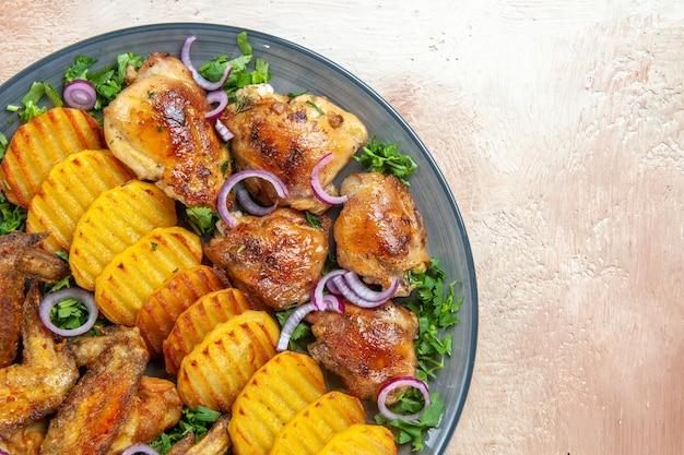 Widok z bliska z góry skrzydełka z kurczaka skrzydełka z kurczaka smażone ziemniaki zioła cebula