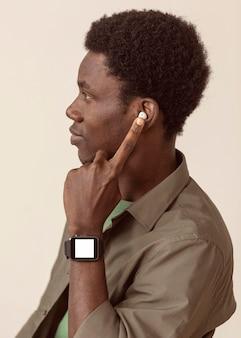 Widok z boku afro-amerykański mężczyzna ubrany w nowoczesne air pods