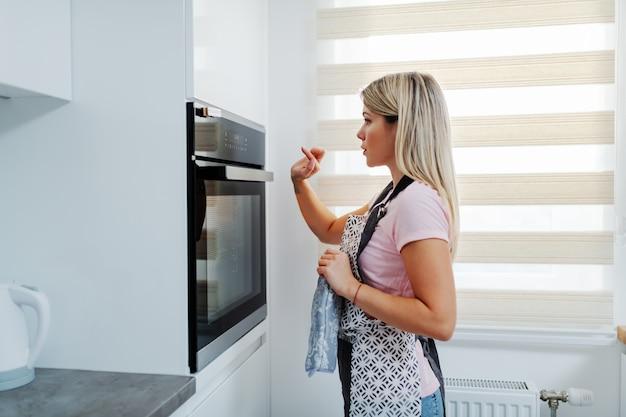 Widok z boku atrakcyjnej blondynki rasy białej w fartuch stojący przed piekarnikiem i dostosowujący temperaturę. wnętrze kuchni