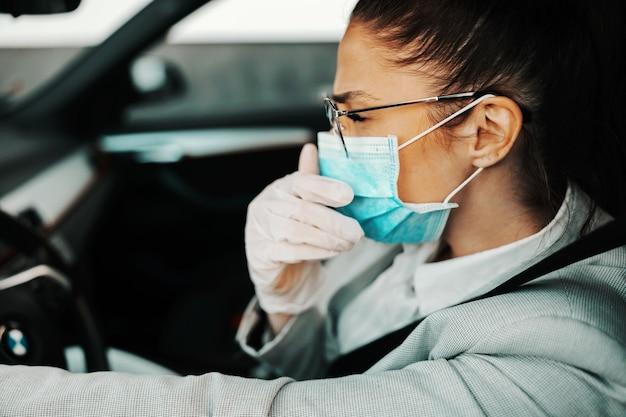 Widok z boku atrakcyjnej brunetki ubranej elegancko, swobodnie z maską i gumowymi rękawiczkami, kaszląc i prowadząc samochód podczas epidemii wirusa covid. a