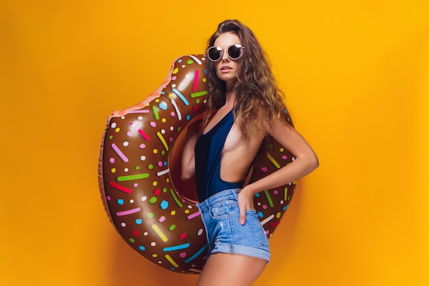 Widok z boku atrakcyjnej młodej kobiety w strojach kąpielowych, modnych okularach przeciwsłonecznych, trzymając pierścień do pływania w kształcie pączka i patrząc na kamery, stojąc na żółto