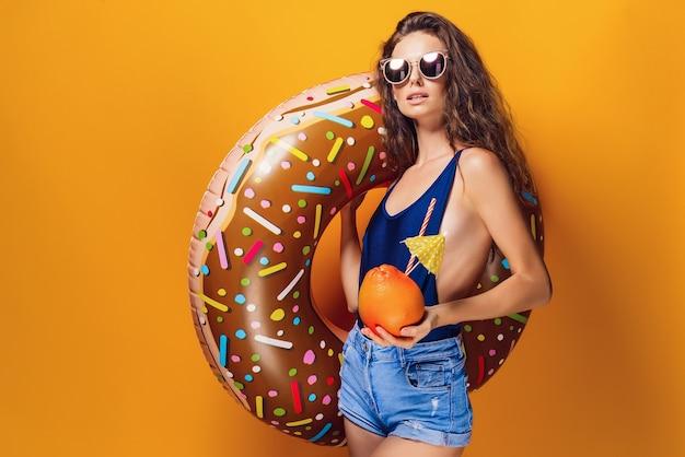 Widok z boku atrakcyjnej młodej seksownej kobiety w strój kąpielowy i niebieskie dżinsy, modne okulary przeciwsłoneczne, trzymając świeży zdrowy napój w grejpfrutach i pierścieniu do pływania w kształcie pączka, stojąc na żółtym