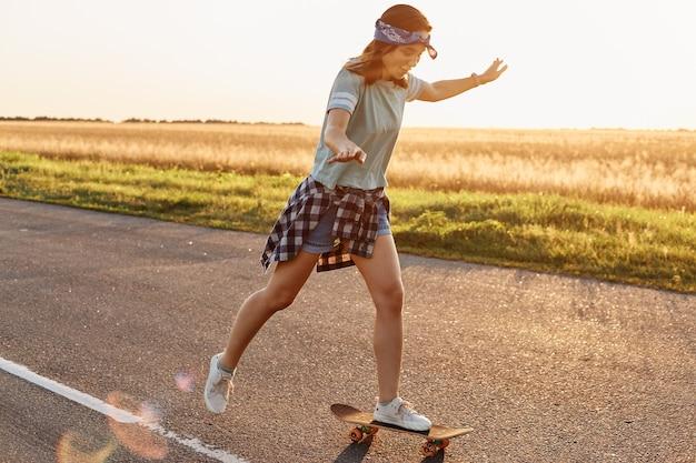 Widok z boku atrakcyjnej szczupłej sportowej kobiety noszącej swobodny strój i pasmo włosów na deskorolce na zewnątrz samotnie o zachodzie słońca, chętnie spędzając czas w sposób aktywny, latem.