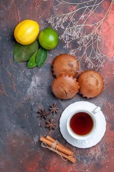 Widok z boku babeczki babeczki owoce cytrusowe z liśćmi filiżanka herbaty z cynamonem