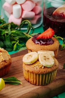 Widok z boku babeczki z truskawkami bananowymi na desce z miętą