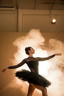 Widok z boku baleriny pozowanie z dymem