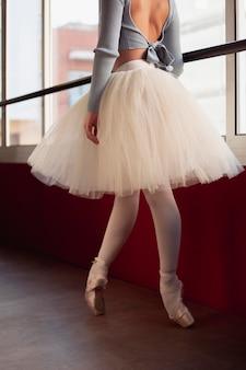 Widok z boku baleriny w spódnicy tutu tańczącej obok okna