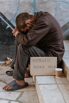 Widok z boku bezdomnego na schodach z filiżanką i znak pomocy