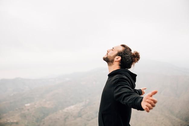 Widok z boku beztroskiego mężczyzny cieszącego się wolnością z rozpostartymi ramionami