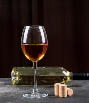 Widok z boku białe wino na czarnym pionie