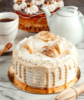Widok z boku białego ciasta ozdobionego roztopioną białą czekoladą bitą śmietaną i bananami na stole