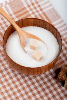 Widok z boku białego cukru w drewnianej misce z łyżką i kawałkami cukru na kraciastym obrusie
