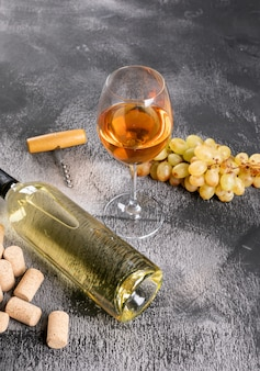 Widok z boku białego wina z winogron na czarnym kamieniu pionowym
