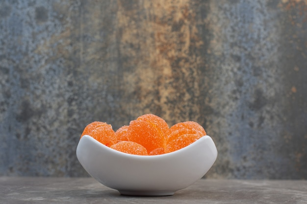 Widok z boku białej ceramicznej miski pełnej pomarańczowych pysznych cukierków.