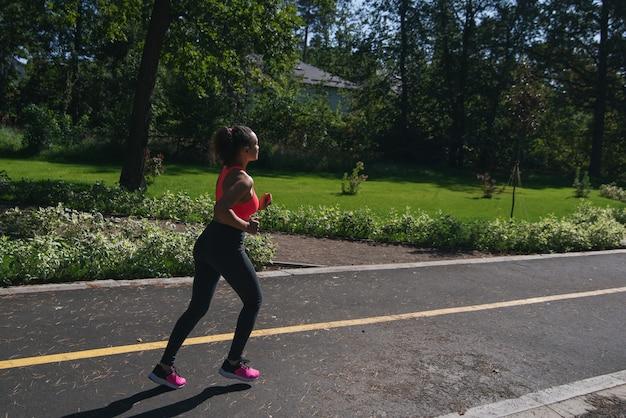Widok z boku biegacza kobieta joggingu na drodze w parku. fitness na świeżym powietrzu