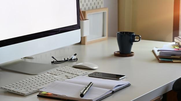 Widok z boku biurowego obszaru roboczego z komputerem, telefonem i materiałami biurowymi.