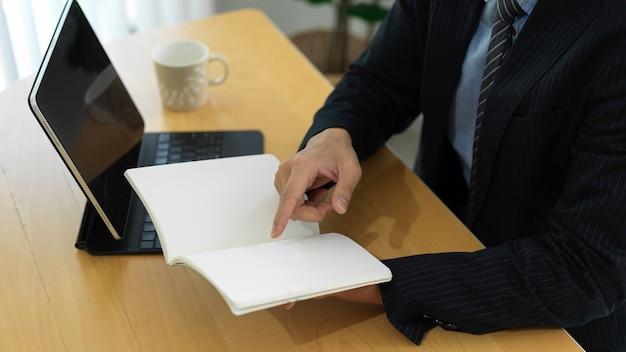 Widok z boku biznesmen czytanie informacji na pustym notatniku podczas pracy z cyfrowym tabletem na stole