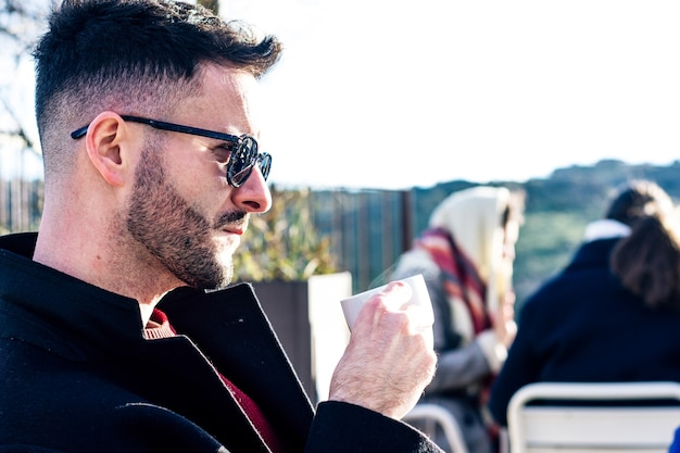 Widok z boku biznesmena z przyciętą brodą i okularami przeciwsłonecznymi po kawie na tarasie baru. zamazani ludzie w tle.