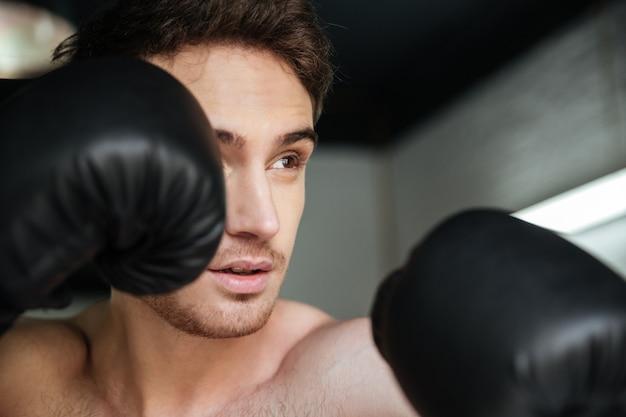 Widok z boku boksera z podniesionymi rękami w goździkach