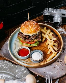 Widok z boku burgera z marynowanymi mięsem wołowym i pomidorami podawany z frytkami i sosami na czarno