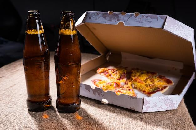 Widok z boku butelek piwa na stole pokrytym jutą obok kartonowego pudełka na wynos pizzy z otwartą pokrywką