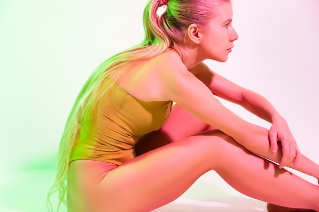 Widok z boku całego ciała wyczerpanej młodej gimnastyczki w body, siedzącej na podłodze i dotykającej bosych stóp podczas odpoczynku po treningu w studio
