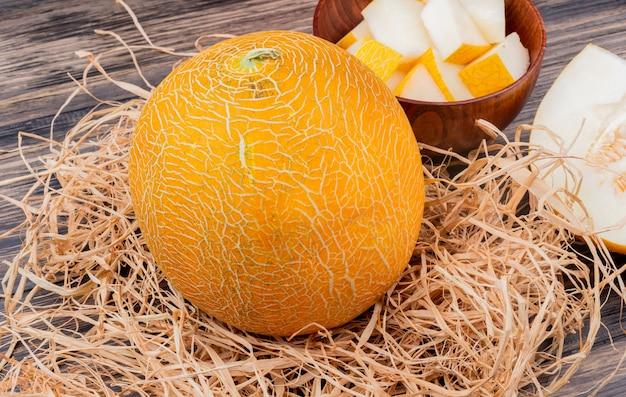 Widok z boku całego melona na słomie z plastrami melona w misce i pokroić jeden na podłoże drewniane