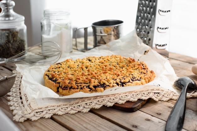 Widok z boku całego tartego ciasta na arkuszu pergaminu otoczonego naczyniami kuchennymi na drewnianym stole