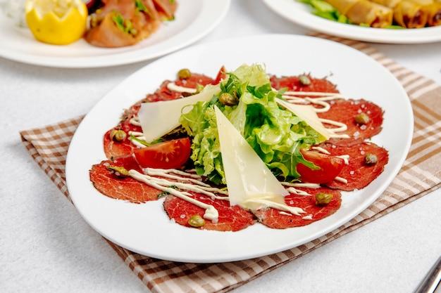Widok z boku carpaccio z wołowiny z parmezanem ruccola i pomidorami