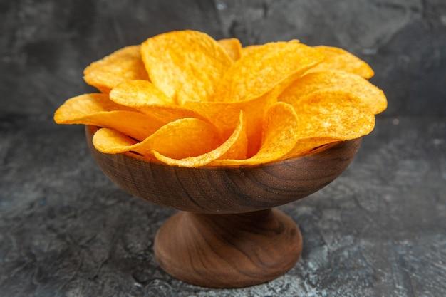 Widok z boku chipsów ziemniaczanych ozdobionych w kształcie kwiatu w brązowej misce na szarym stole