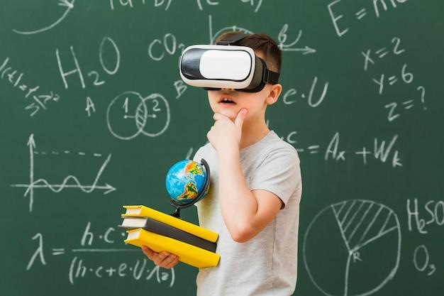 Widok z boku chłopca na sobie słuchawki wirtualnej rzeczywistości i trzyma książki