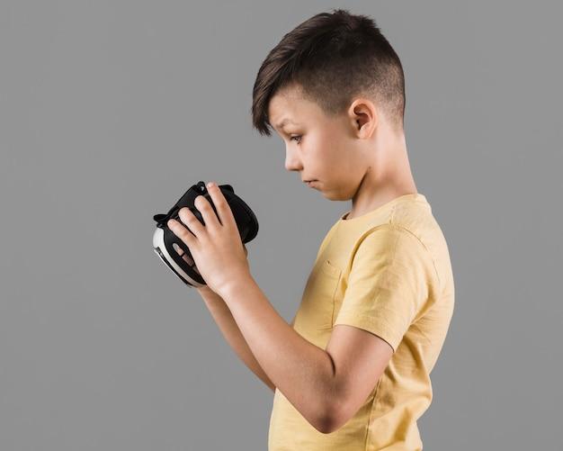 Widok z boku chłopca patrząc przez zestaw słuchawkowy rzeczywistości wirtualnej