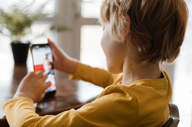 Widok z boku chłopca przy użyciu smartfona w domu