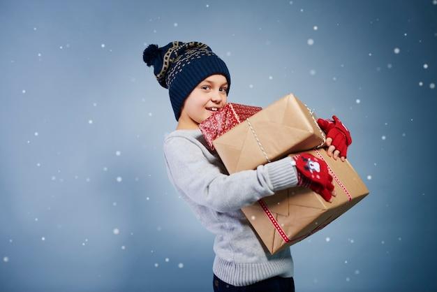 Widok z boku chłopca trzymającego prezent na boże narodzenie