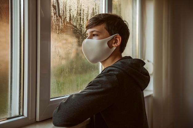 Widok z boku chłopca z maską patrząc przez okno