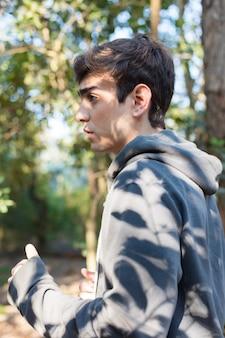 Widok z boku chłopca z szarą bluzę z rzędu