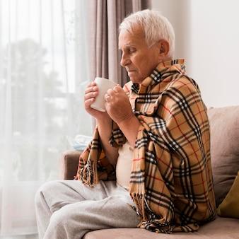 Widok z boku chory mężczyzna trzyma kubek
