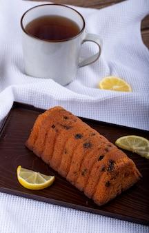 Widok z boku ciasta z rodzynkami z plasterkami cytryny na drewnianej desce i kubkiem herbaty na obrusie