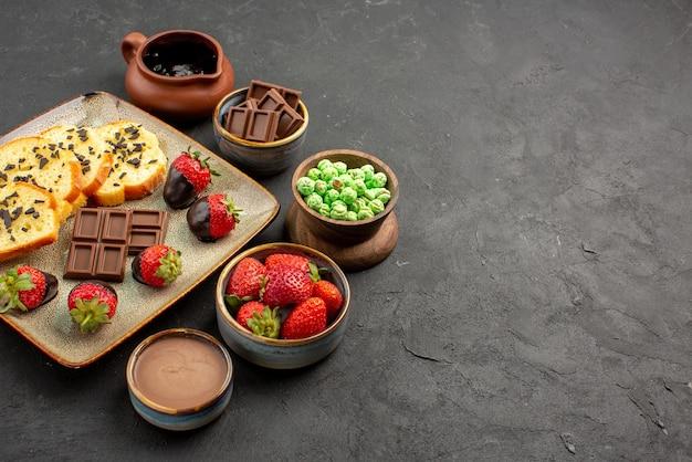 Widok z boku ciasto truskawkowe czekoladowe apetyczne ciasto i truskawki miski czekoladowych truskawek zielone cukierki i krem czekoladowy po lewej stronie stołu