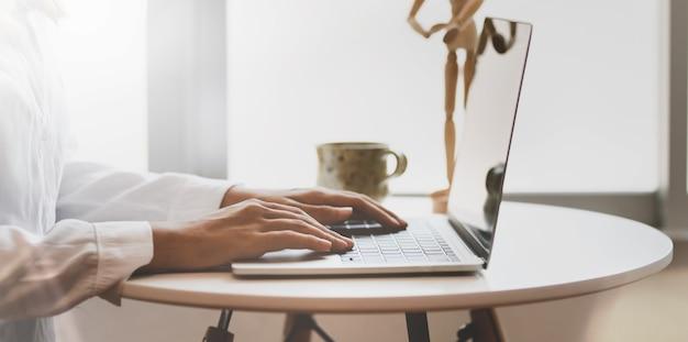 Widok z boku close-up z kobiecej ręki pisarza pisania na laptopie