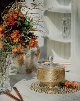 Widok z boku cukiernicy z kwiatami w wazonie na ścianie