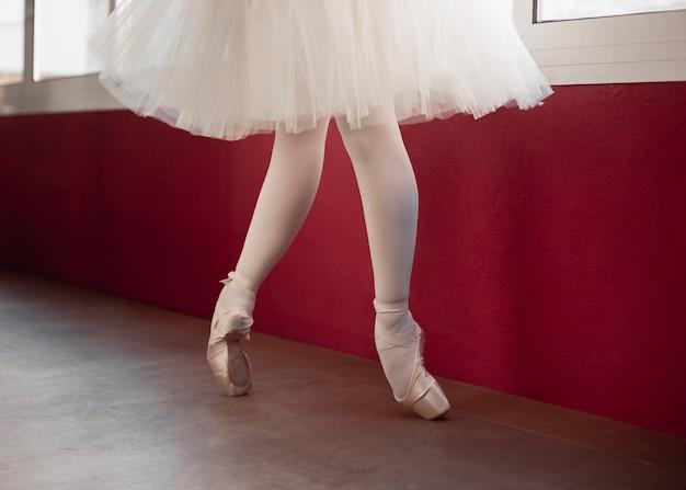 Widok z boku ćwiczącej baleriny w spódnicy tutu obok okna