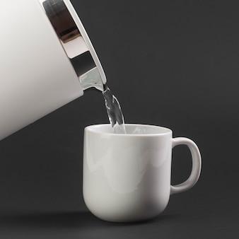 Widok z boku czajnik elektryczny wlewający wodę do filiżanki