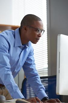 Widok z boku czarnego człowieka czyta ważny e-mail na swoim biurowym komputerze